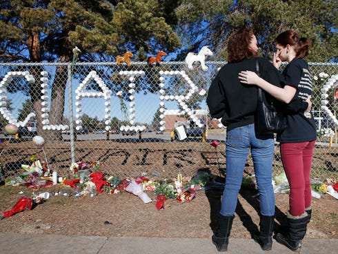 Arapahoe High School junior Emily Evans, right, and her mother Cristina hug while visiting a makeshift memorial bearing the name of wounded student Claire Davis, who was shot by a classmate three days earlier, in front of Arapahoe High School in Cent