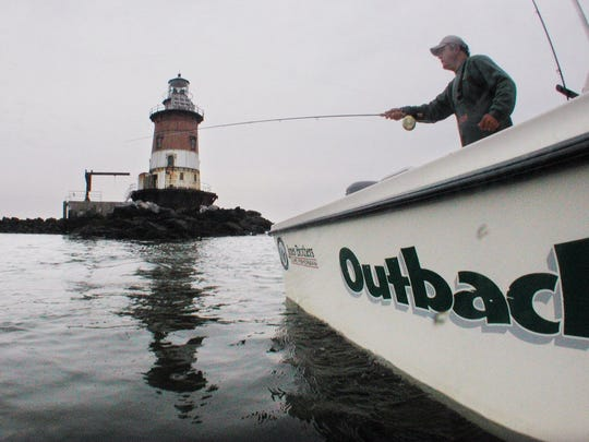 Captain Bill Hoblitzell of Outback Fishing Charters makes a cast with his flyrod near the Romer Shoal Light.