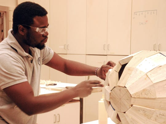 Folk artist Eric Adjetey Anang of Ghana helped Iowa State University students make a corn-shaped coffin during a September workshop in Ames.