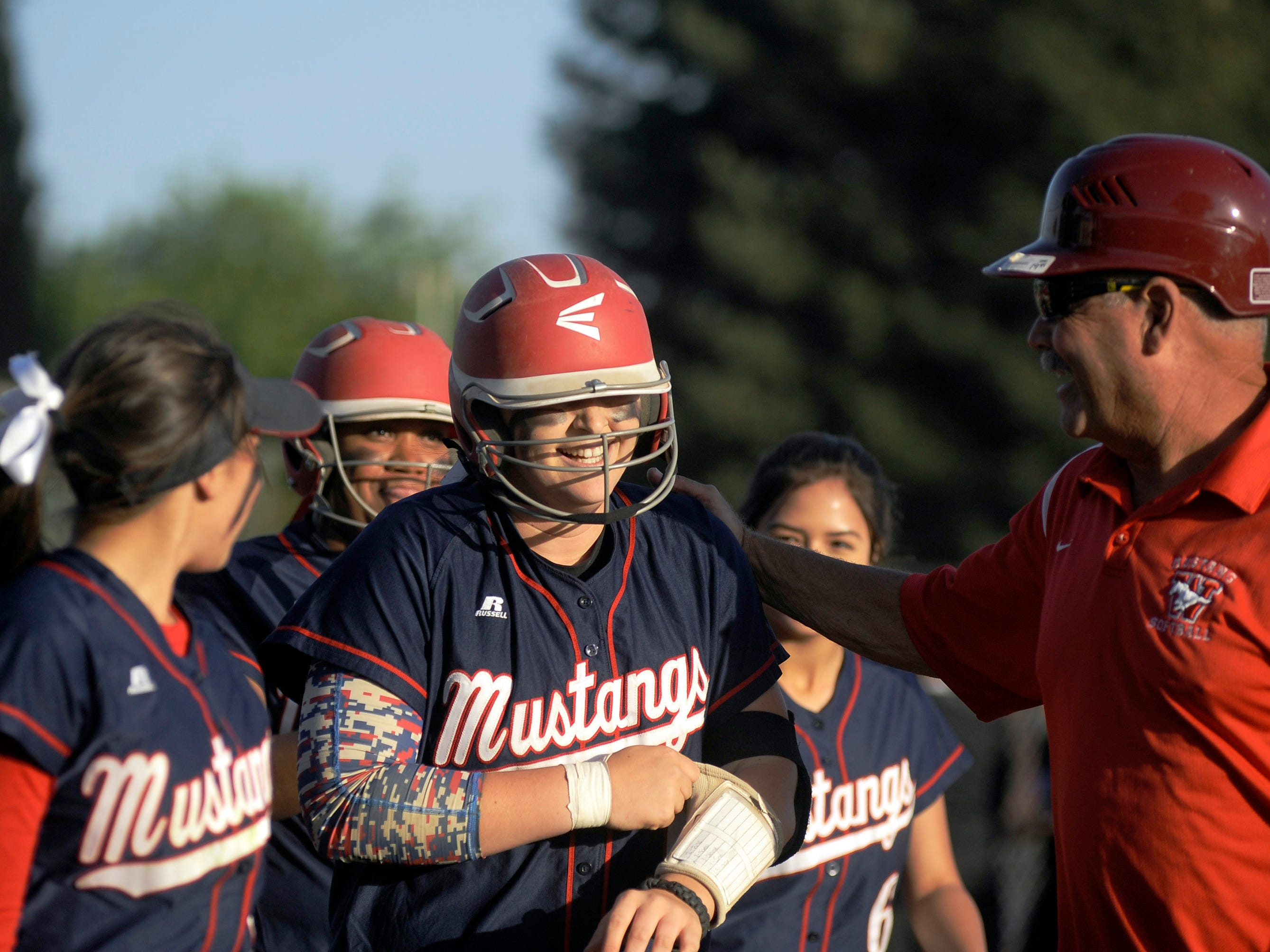 Tulare Western's Kelcey Carrasco, center, is greeted at home plate after her walk-off home run in Tuesday's game against Mission Oak.