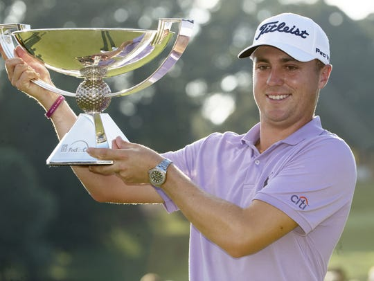 Justin Thomas hoists the trophy after winning the FedEx