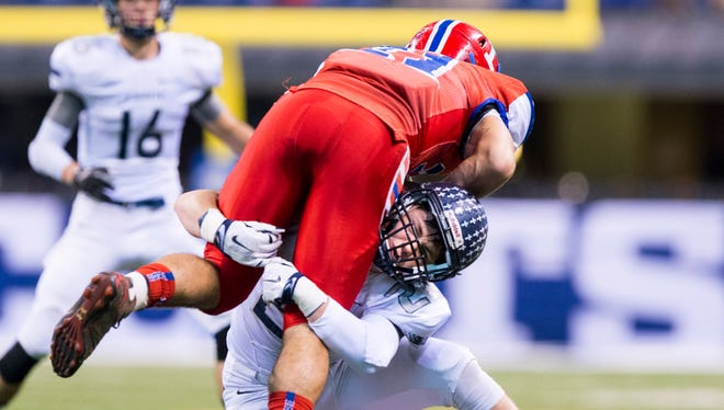 Lafayette Central Catholic junior Jacob Page (22) hits Linton-Stockton senior Mitch Eberhardt (21) as he returns a kickoff during the first half of the IHSAA Class 1A State Championship high school football game, Nov. 27, 2015, in Indianapolis.