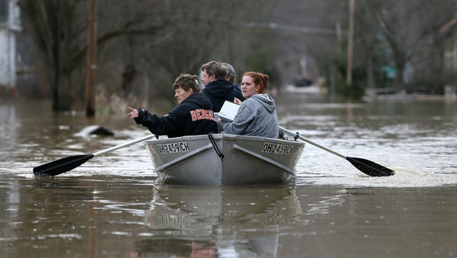 Lesa Tomlin, left, gestures toward dry land as Lori Sullender, right, holds medicine for her father-in-law pulled from a Rohde Avenue home in California, Sunday, Feb. 25, 2018, in Cincinnati. The Ohio River is expected to crest at 60.7 feet by Sunday evening, according to the National Weather Service. The river rose above the 60 feet mark for the first time in two decades Sunday morning.