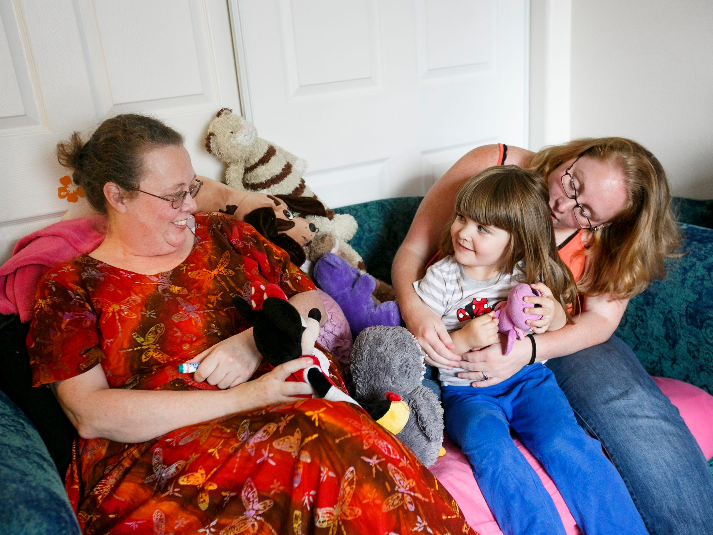 Mia Storm holds her daughter Lily, 3, as they spend time with Mia's mother Penny Woods. Woods gave Mia up to the state in 1988 while experiencing mental health problems. Storm, now 32, and her mother reconnected recently and have been working to rebuild their relationship.