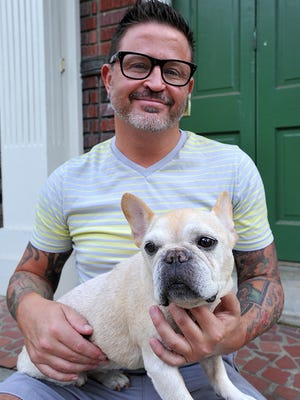 David Brownman holds his French bulldog, bitsy, outside his home in Belhaven.