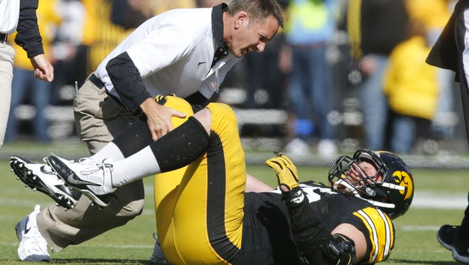 Iowa trainers check on defensive end Drew Ott after he injured his right knee against Illinois on Saturday.