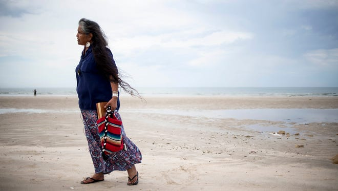 Thomasa Rivas stands on a beach in Puerto Peñasco, Sonora, after praying at the ocean. She will travel to the Vikita Ceremony, where tribal members pray for the earth and everyone and everything on it.