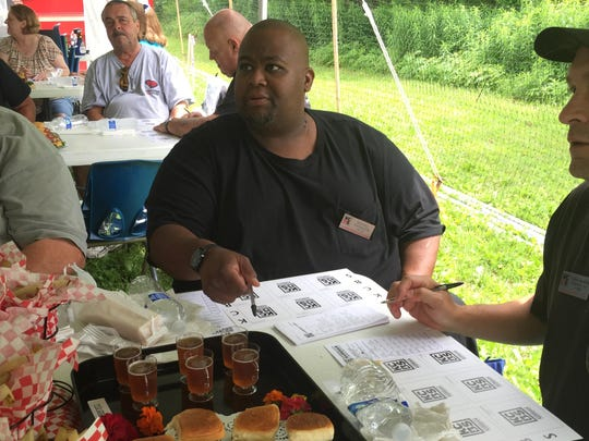 Michael Thomason of Colchester prepares to judge burgers during the Not Quite Independence Day barbecue competition Saturday in Waterbury.