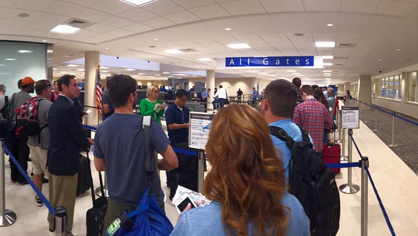 Passengers line up to go through security at GSP