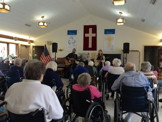 Nick Hoover and Jess Holland sing folk music for residents