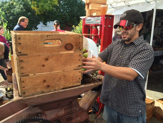 Joseph Woolley tosses a bucket of apples into a century-old