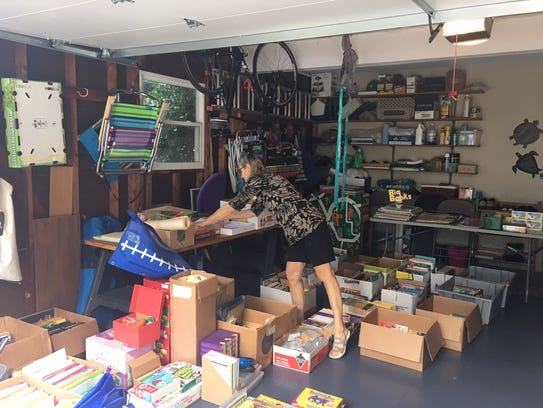 Sky McClain rearranges a box in her garage on Monday.