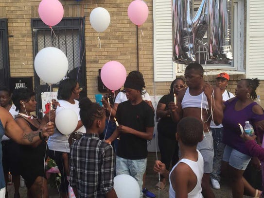 Vigil participants prepare to release balloons as a