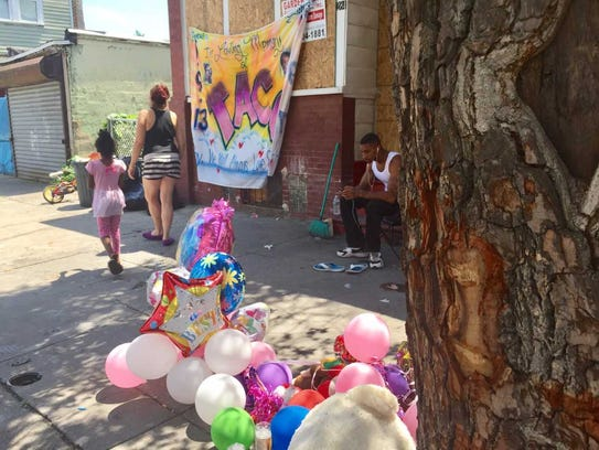 A woman and a child walk past a  memorial for Layannie
