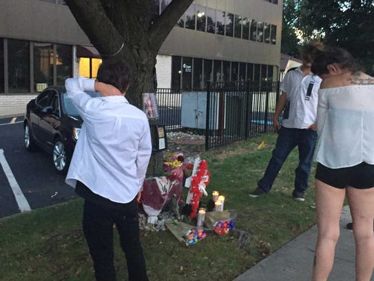 Participants at a vigil Sunday look at a memorial to