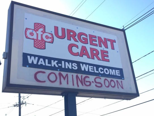 A sign notes the pending arrival of an AFC Urgent Care