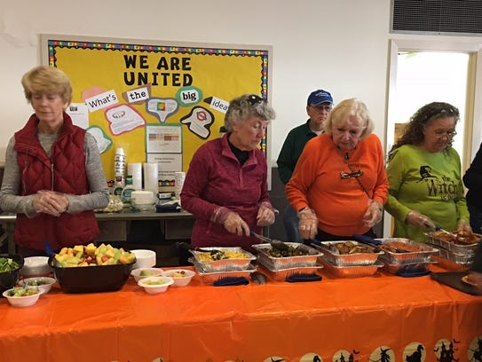 Volunteers serve food at the luncheon marking Tom O'Leary's