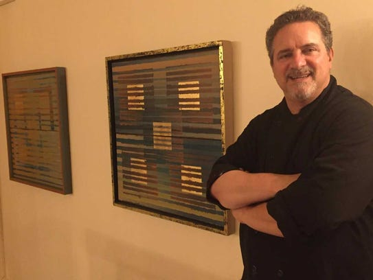 Mark Raab stands by one of his paintings in Braise