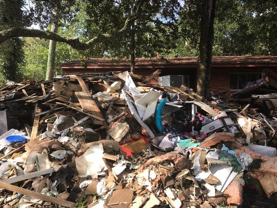 Storm debris outside a home in Beaumont, Texas. The hard-hit town about 90 miles from Houston is one of the places superstorm Sandy survivors have delivered supplies.