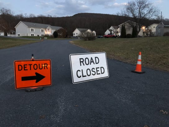 Road-closed and detour signs are seen on Mountain Shadow