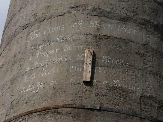 "The silo bears the ""Five aims of the farm."""