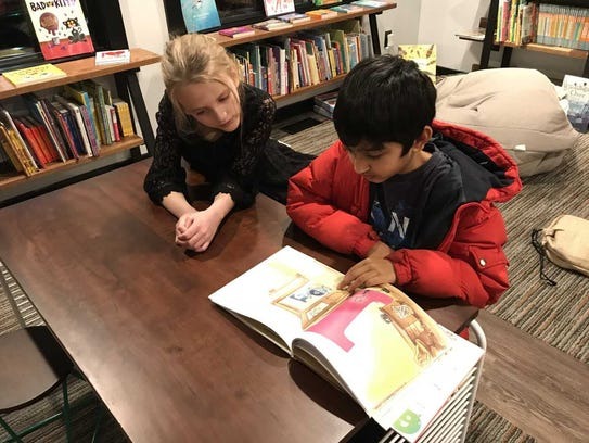 Skye Nicoll, 8, and Atiksh Bordia, 10, read a children's