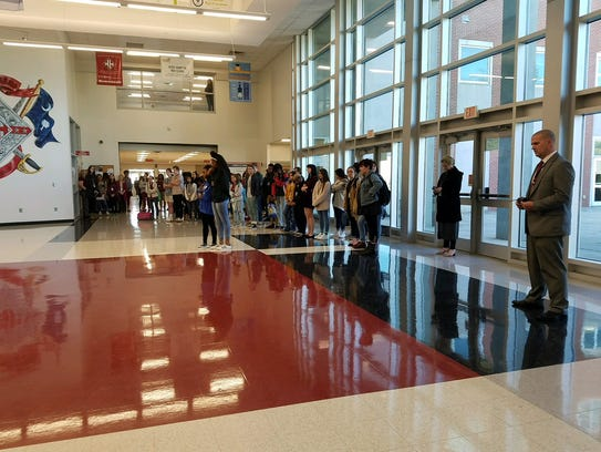 School officials line the doorways to the outside at