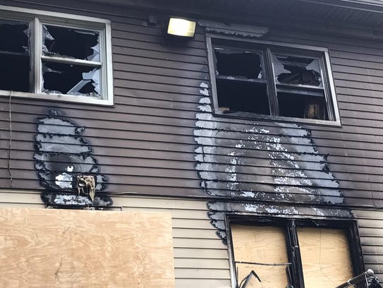 The charred exterior of a two-family home damaged by