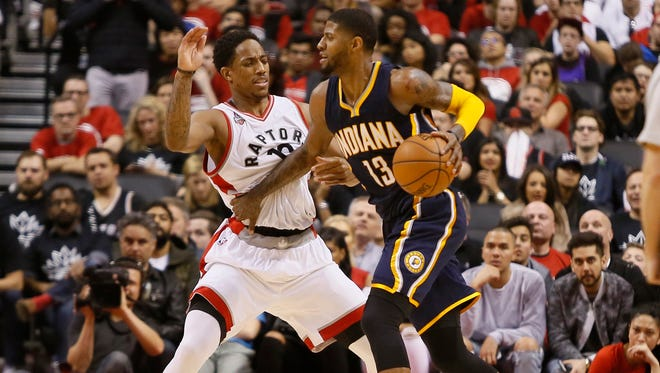 Pacers forward Paul George dribbles past Raptors guard DeMar DeRozan (10) in game one of the first round of the 2016 NBA Playoffs at Air Canada Centre.