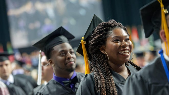 A student smiles as she enters Bramlage Coliseum during the commencement ceremony for Kansas State University's College of Arts and Sciences on May 14, 2016.