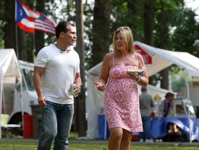 Hernando Perez and wife Kimberly Perez have a plate of traditional Puerto Rican food from a vendor at the Puerto Rican Festival of NJ, Wednesday, Jul. 23, 2014 in Vineland.  Staff Photo/Sean M. Fitzgerald