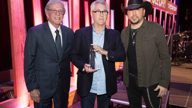 Bob Kingsley, Clarence Spalding and Jason Aldean on stage at the Grand Ole Opry House.