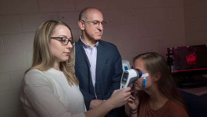 Docia Demmin (left) and Steven Silverstein demonstrate how the hand-held device RETeval may prove to be a more accessible way to diagnose schizophrenia, predict relapse and symptom severity, and assess treatment effectiveness.