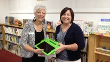 Gail Sheldon, director of the Somerset County Library System, left, accepts two iPads from Marlena Turner of the Somerset County Judy Center.