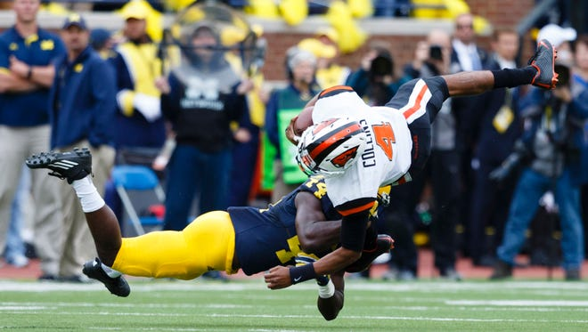 Sep 12, 2015; Ann Arbor, MI, USA; Oregon State Beavers quarterback Seth Collins (4) is tackled by Michigan Wolverines safety Delano Hill (44) in the second quarter at Michigan Stadium. Mandatory Credit: Rick Osentoski-USA TODAY Sports