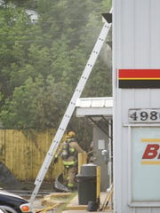 Smoke billowing out of the auto parts store on Old U.S. 23 prompts Michigan State Police to keep bystanders at a distance Wednesday, July 11, 2018 over concerns about hazardous materials burning.