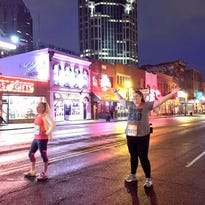Runners pose for pictures as the start of the Country Music Marathon approaches.