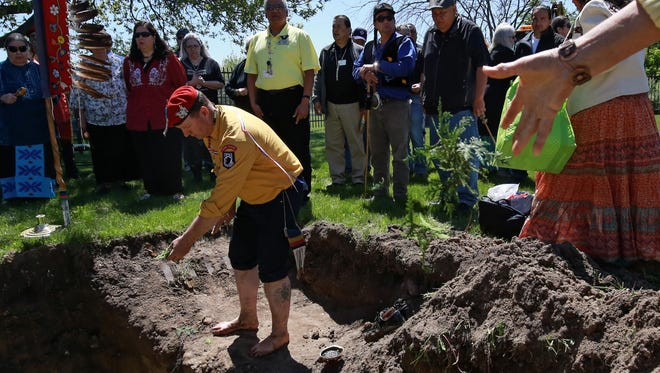 Saginaw Chippewa tribe member Tony Perry of Elwell tosses cedar into a grave during a burial ceremony for the remains of 43 ancestors at Nibokaan Indian Cemetery in Mt. Pleasant in May. Tribe members traveled to New York, Toledo and Dearborn to reclaim the remains.