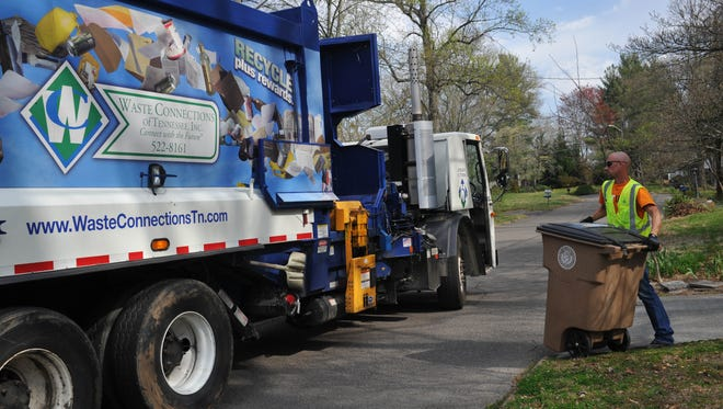 Waste Connections of Tennessee worker Brandon Roberts empties a recycling bin on April 9, 2013, off Francis Road in West Knoxville.