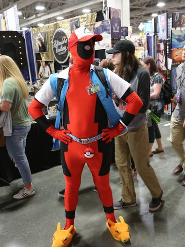 A Deadpool / Pokemon cosplayer poses for a photo at