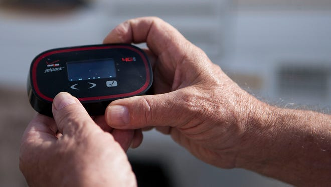 """Ken and Vicki Kaas use what they call a Verizon """"jet pack"""" MiFi system for internet and Wifi connection while camping at International Raceways in Avondale Ariz., Wednesday March 11, 2015."""