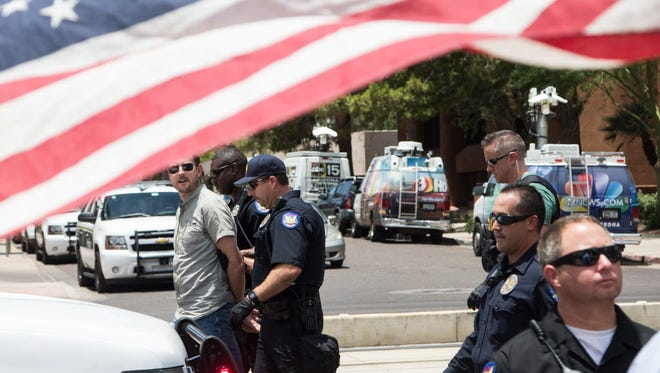 One of four people arrested after immigration-reform advocates blocked the Central Avenue in downtown, Phoenix, Ariz.
