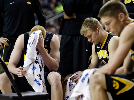Iowa's Aaron White, left, and teammates rest during