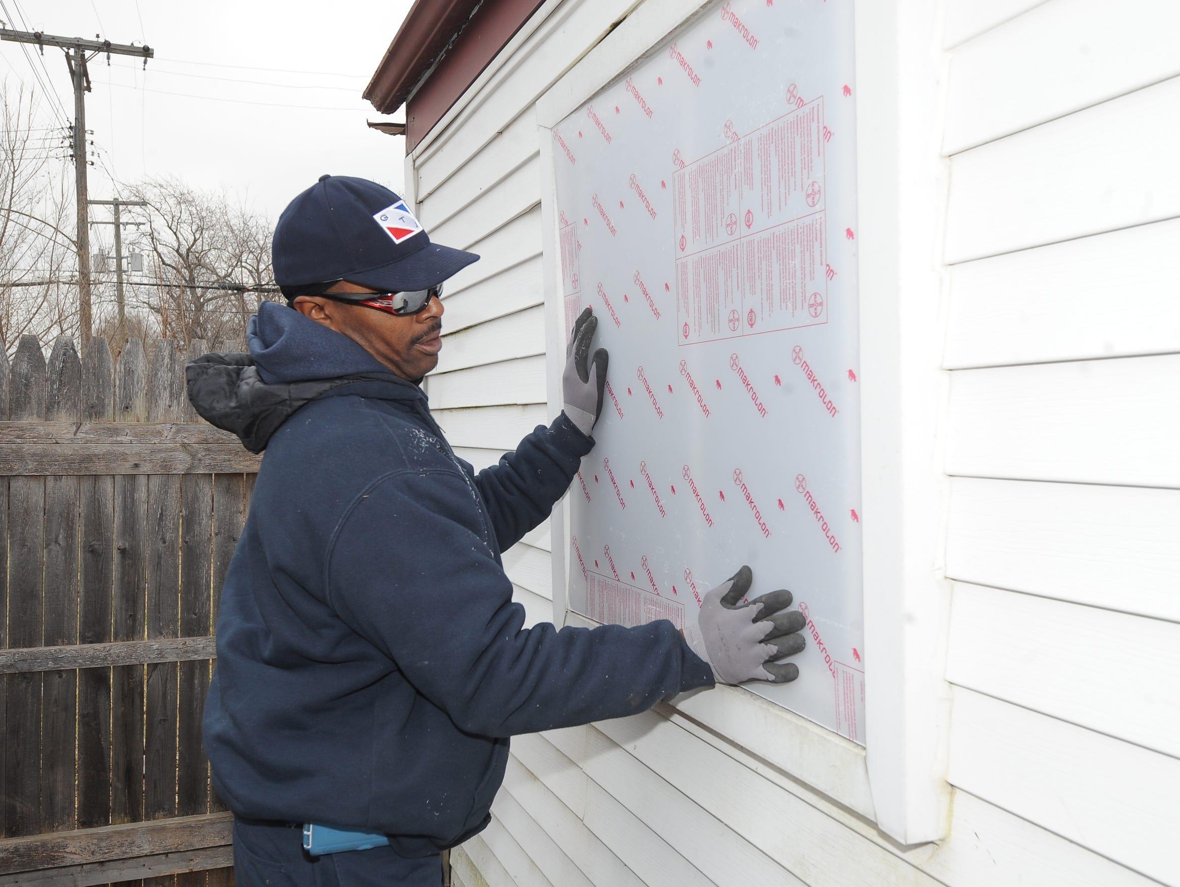 Willie Jackson, of GTJ Construction, installs material