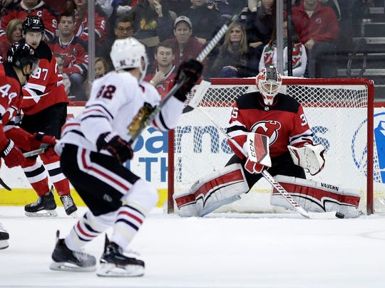 New Jersey Devils goalie Cory Schneider right, deflects a shot by the Chicago Blackhawks during the second period of an NHL hockey game, Saturday, Dec. 23, 2017, in Newark, N.J.