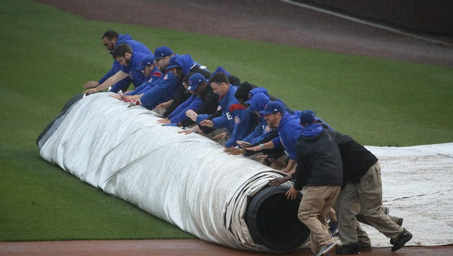 Members of the Cubs ground crew roll out the tarp in the sixth inning.