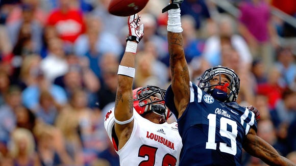 Mississippi's Derrick Jones (19) misses a catch under pressure by Louisiana-Lafayette's Dominick Jones (20) in the first half of an NCAA college football game against Louisiana-Lafayette in Oxford, Miss., Saturday, Sept. 13, 2014. (AP Photo/The Commercial Appeal, Jim Weber)