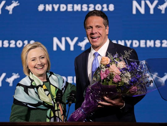 Former Secretary of State and former Democratic Presidential candidate Hillary Clinton, left, is greeted by Gov. Andrew Cuomo after speaking during the New York state Democratic convention on Wednesday, May 23, 2018, in Hempstead, N.Y.