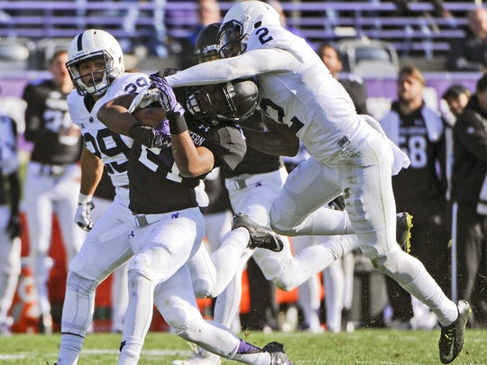 Northwestern running back Justin Jackson (21) runs against Penn State safety Marcus Allen (2) and cornerback John Reid (29)  during the second half of an NCAA college football game in Evanston, Ill.,  Saturday, Nov. 7, 2015.