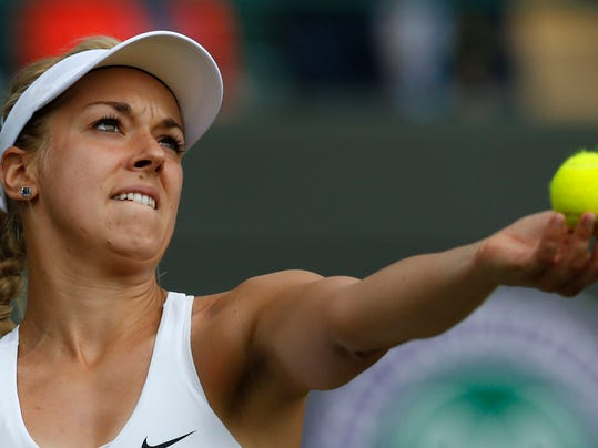 Sabine Lisicki of Germany prepares to serve to Ana Ivanovic of Serbia during their women's singles match at the All England Lawn Tennis Championships in Wimbledon, London, Monday, June 30, 2014. (AP Photo/Ben Curtis)